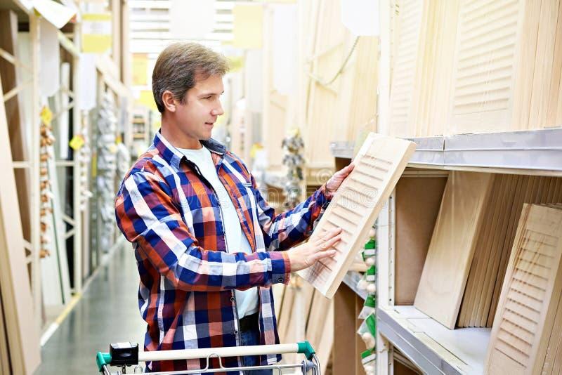 El hombre elige las fachadas de madera para los muebles en tienda foto de archivo libre de regalías