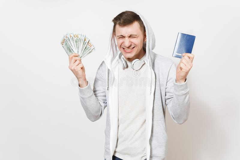 El hombre emocionado extático joven en camiseta, camiseta ligera con la capilla con los auriculares sostiene el pasaporte interna imagen de archivo libre de regalías