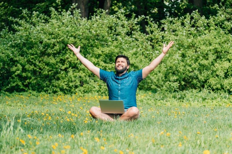 El hombre emocionado feliz con las manos aumentadas ordenador portátil para arriba celebra éxito foto de archivo