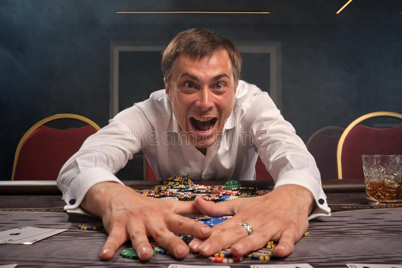 El hombre emocional hermoso está jugando el póker que se sienta en la tabla en casino foto de archivo libre de regalías