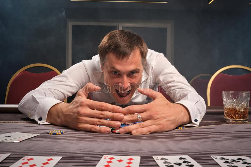 El hombre emocional hermoso está jugando el póker que se sienta en la tabla en casino imagen de archivo
