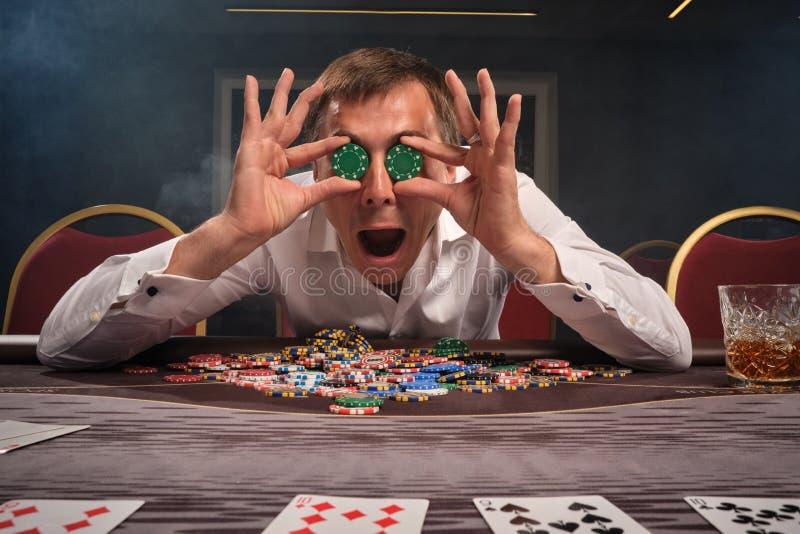 El hombre emocional hermoso está jugando el póker que se sienta en la tabla en casino imagen de archivo libre de regalías
