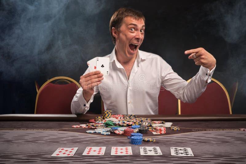 El hombre emocional hermoso está jugando el póker que se sienta en la tabla en casino imagenes de archivo