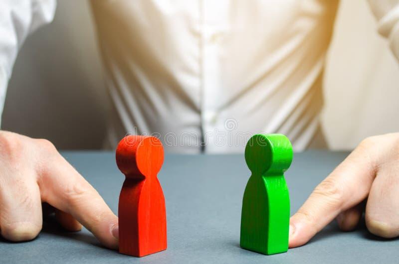 El hombre empuja las figuras rojas y verdes el uno al otro La búsqueda para un compromiso, mediación en negociaciones Encanto de  fotos de archivo libres de regalías