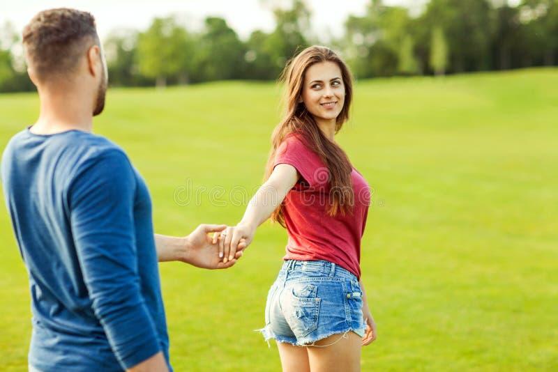 El hombre en el amor que lleva a cabo la mano de una muchacha y ellos caminan en el parque imagen de archivo libre de regalías
