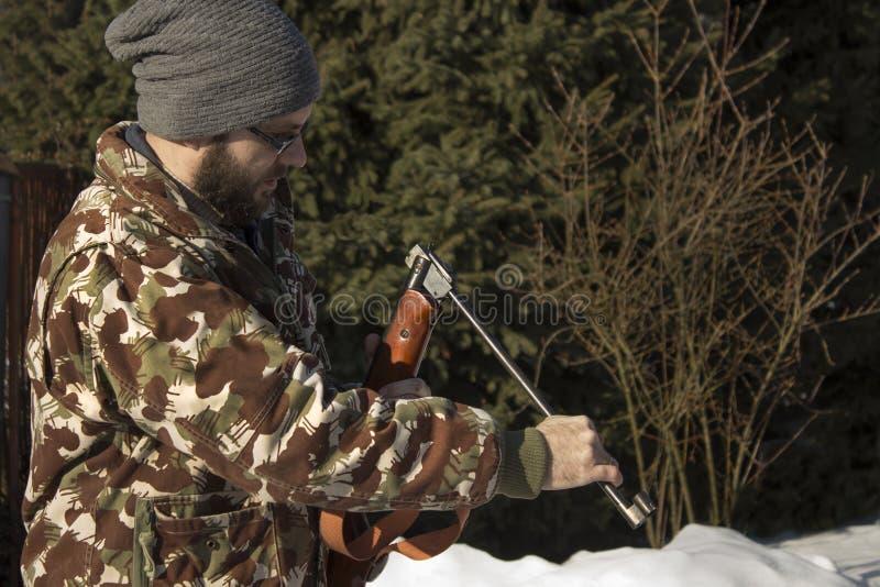 El hombre en bosque del invierno recarga las armas neumáticas El cazador se vistió en camuflaje con el arma neumático, rifle foto de archivo