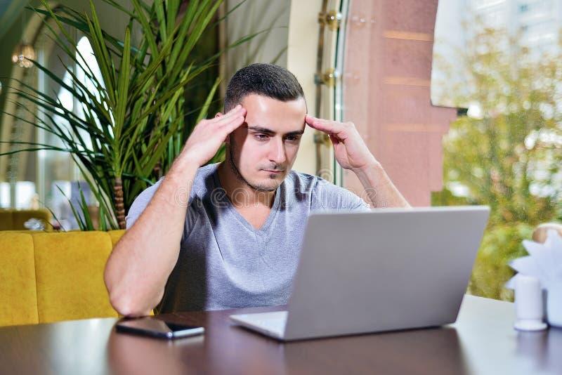 El hombre en café está trabajando y está pensando foto de archivo