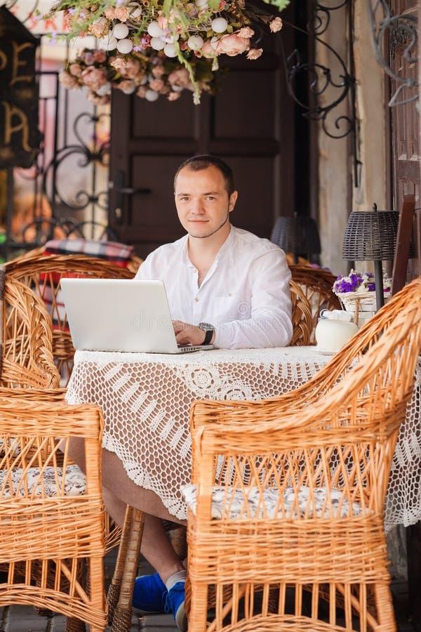 El hombre en caffee trabaja en su ordenador portátil fotografía de archivo libre de regalías