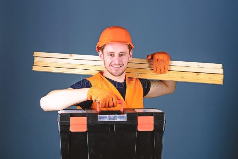 El hombre en el casco, casco lleva a cabo la caja de herramientas y los haces de madera, fondo gris Carpintero, trabajador, const fotografía de archivo