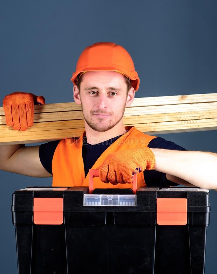 El hombre en el casco, casco lleva a cabo la caja de herramientas y los haces de madera, fondo gris Concepto profesional del carp fotografía de archivo