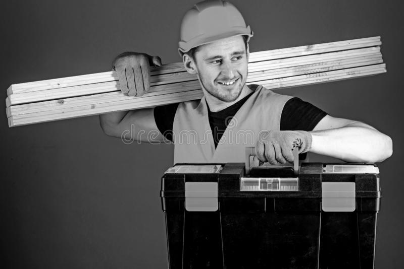 El hombre en el casco, casco lleva a cabo la caja de herramientas y los haces de madera, fondo gris Concepto profesional del carp foto de archivo libre de regalías