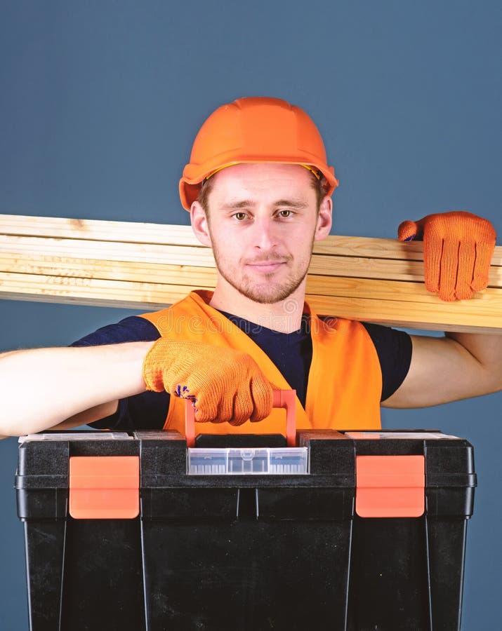 El hombre en el casco, casco lleva a cabo la caja de herramientas y los haces de madera, fondo gris Concepto profesional del carp imagen de archivo libre de regalías