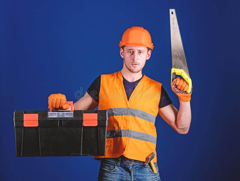 El hombre en el casco, casco lleva la caja de herramientas y sostiene el handsaw, fondo azul Concepto del carpintero Trabajador,  foto de archivo