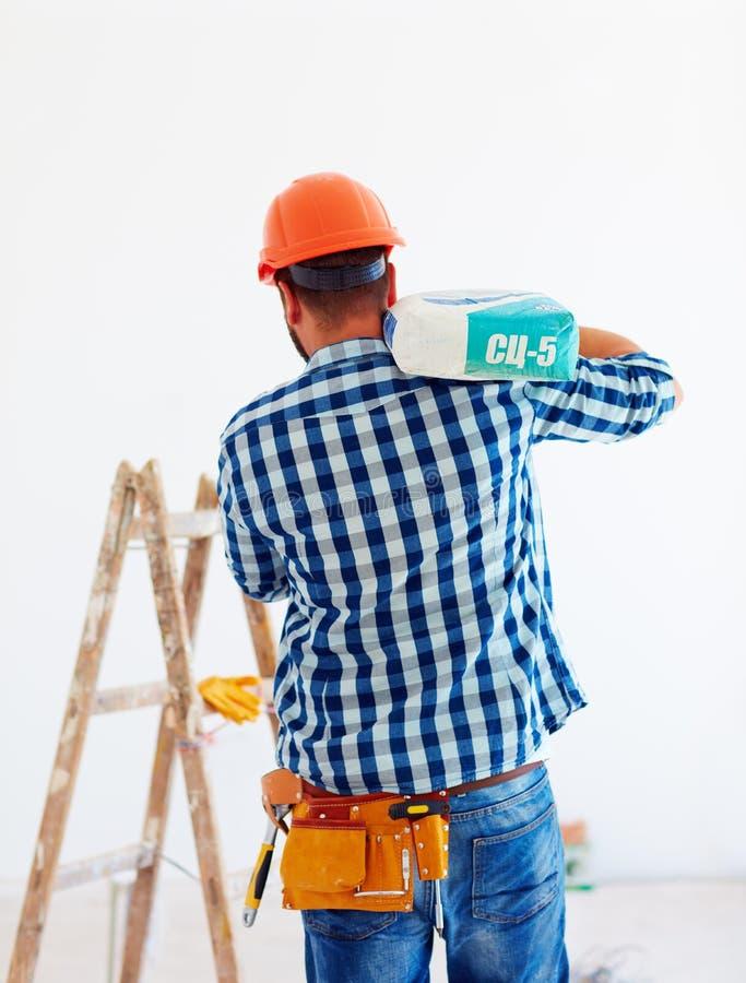 El hombre en casco lleva un bolso del cemento para el propósito de la construcción imagen de archivo libre de regalías