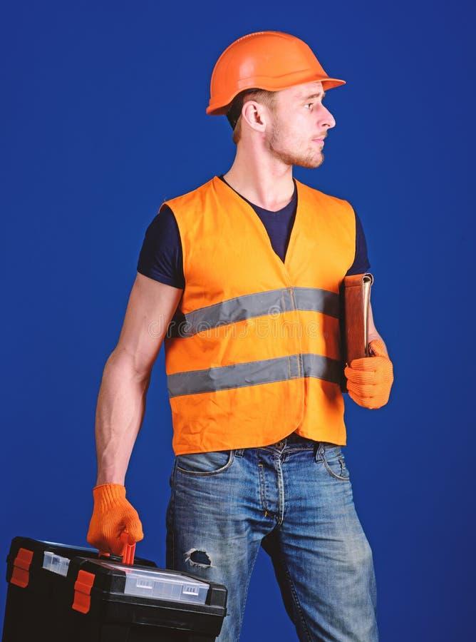 El hombre en el casco, casco sostiene la caja de herramientas y la carpeta con los documentos, fondo azul Reparador listo para tr imagenes de archivo