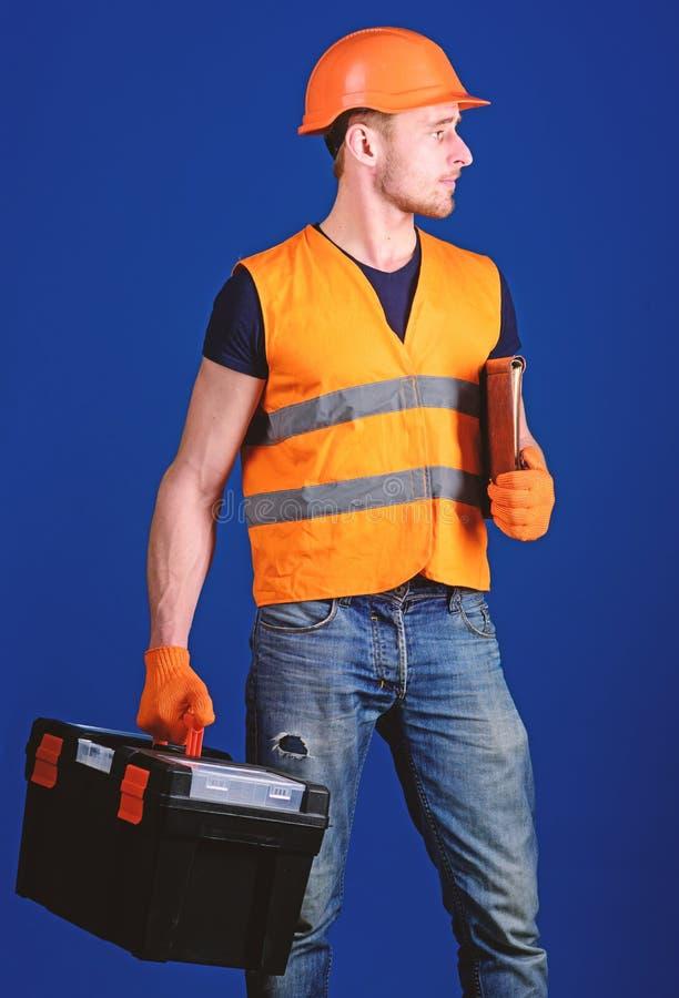 El hombre en el casco, casco sostiene la caja de herramientas y la carpeta con los documentos, fondo azul Reparador listo para tr imagen de archivo libre de regalías