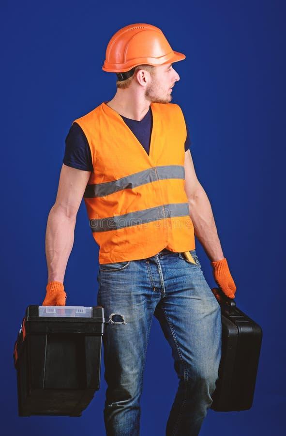 El hombre en el casco, casco sostiene la caja de herramientas y la maleta con las herramientas, fondo azul Concepto equipado del  fotografía de archivo libre de regalías