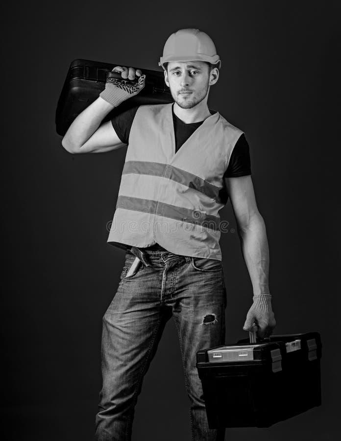 El hombre en el casco, casco sostiene la caja de herramientas y la maleta con las herramientas, fondo azul Concepto equipado del  fotos de archivo