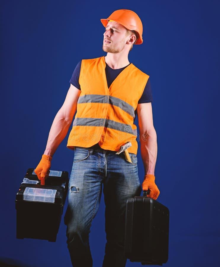 El hombre en el casco, casco sostiene la caja de herramientas y la maleta con las herramientas, fondo azul La manitas, reparador  imagenes de archivo