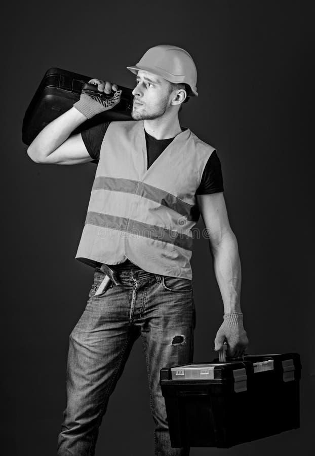 El hombre en el casco, casco sostiene la caja de herramientas y la maleta con las herramientas, fondo azul Trabajador, manitas, r fotografía de archivo libre de regalías