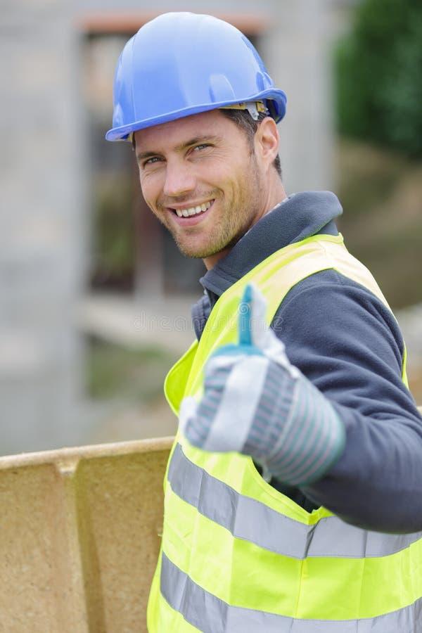 El hombre en casco y guante protector muestra el pulgar encima del gesto foto de archivo