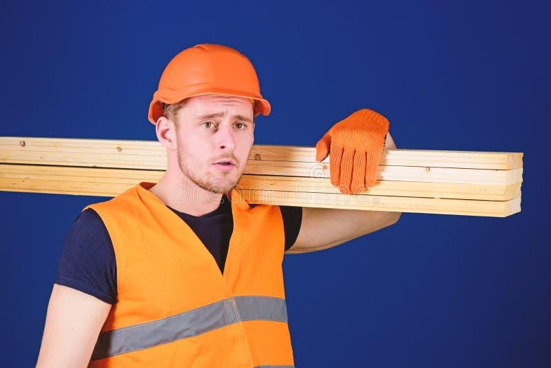 El hombre en casco, casco y guantes protectores lleva a cabo el haz de madera, fondo azul Concepto de madera de los materiales ca fotografía de archivo