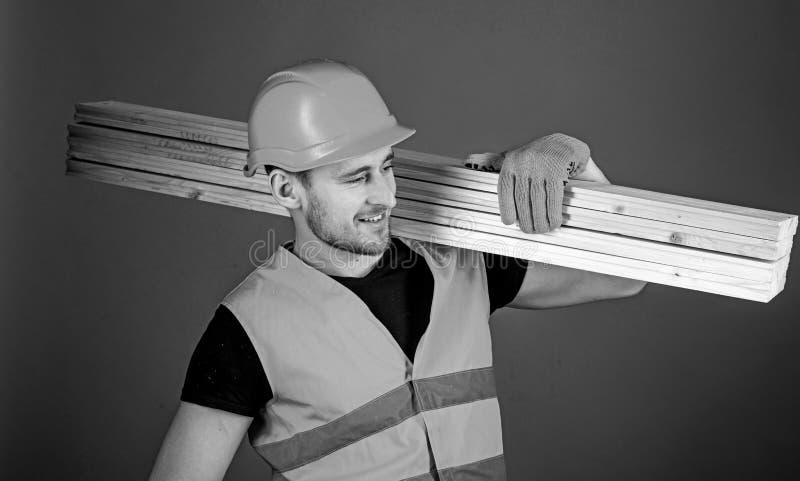 El hombre en casco, casco y guantes protectores lleva a cabo el haz de madera, fondo gris Carpintero, carpintero, trabajador imagen de archivo