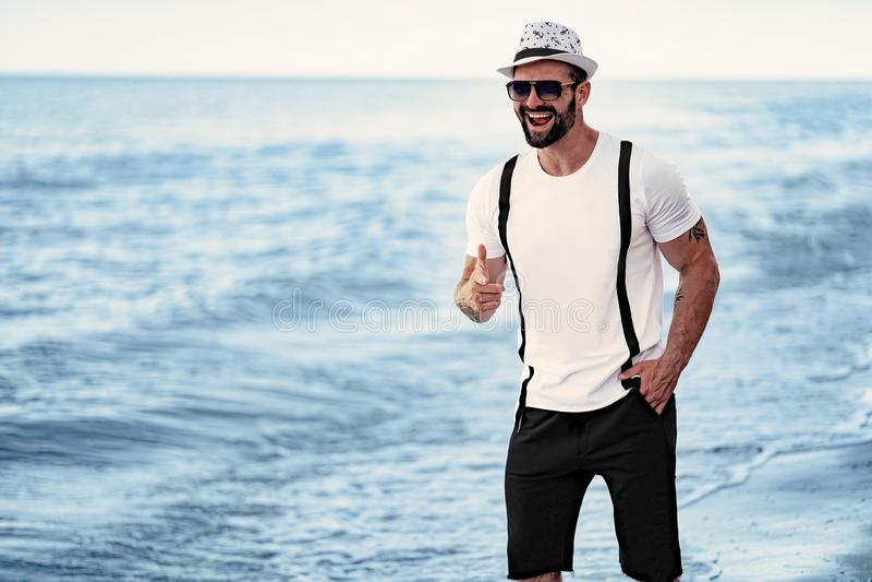 El hombre en el centro turístico en un azul de la camisa y gafas de sol, sombrero en el fondo del mar fotos de archivo libres de regalías