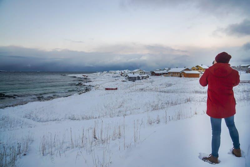 El hombre en chaqueta roja del invierno con los tejanos y el sombrero hecho punto toma las fotografías del paisaje en vacaciones  fotografía de archivo