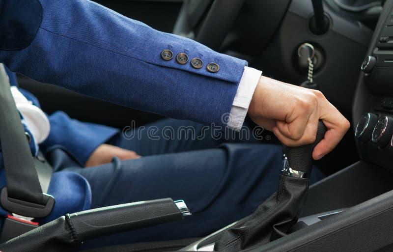 El hombre en el coche está sosteniendo el botón del cambio de la velocidad del ` s del coche imagen de archivo libre de regalías