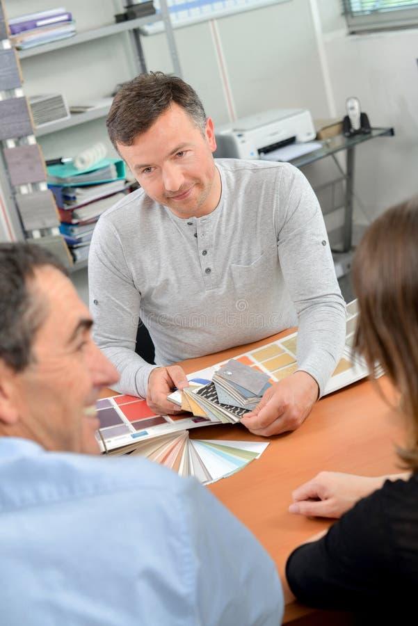 El hombre en el consulation con los pares pinta muestras en el escritorio imagen de archivo libre de regalías