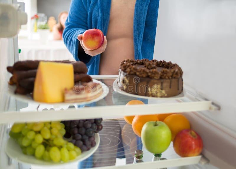 El hombre en dieta toma la manzana sana en vez de la comida dura fotografía de archivo