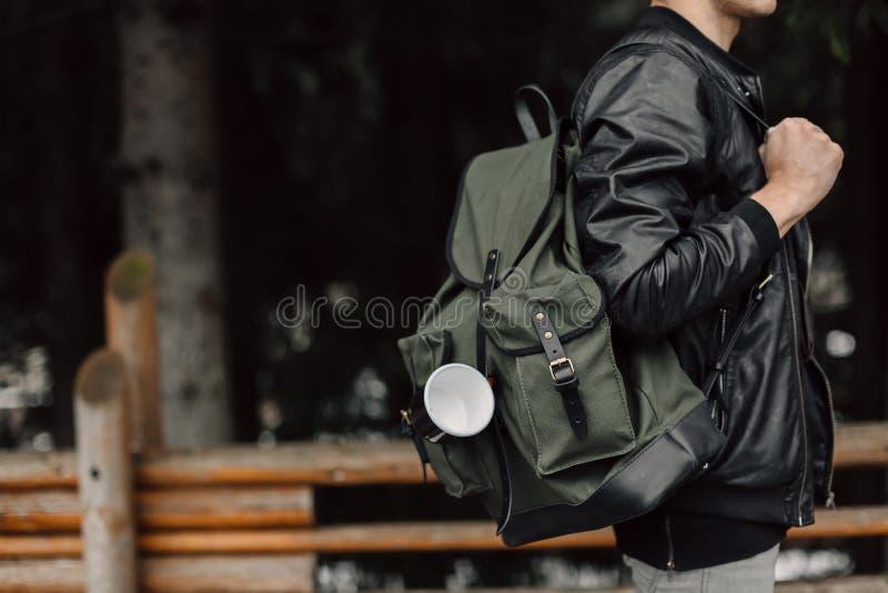 El hombre en el bosque Varón con una mochila negra y una taza imagenes de archivo