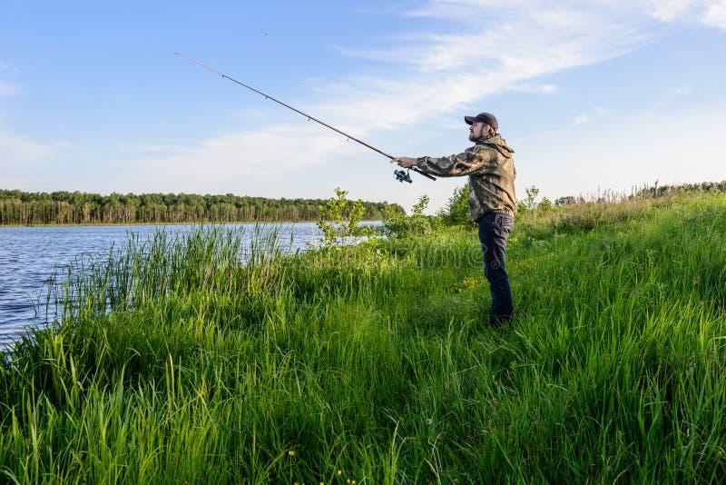 El hombre en el río lanza una pesca de giro imagenes de archivo