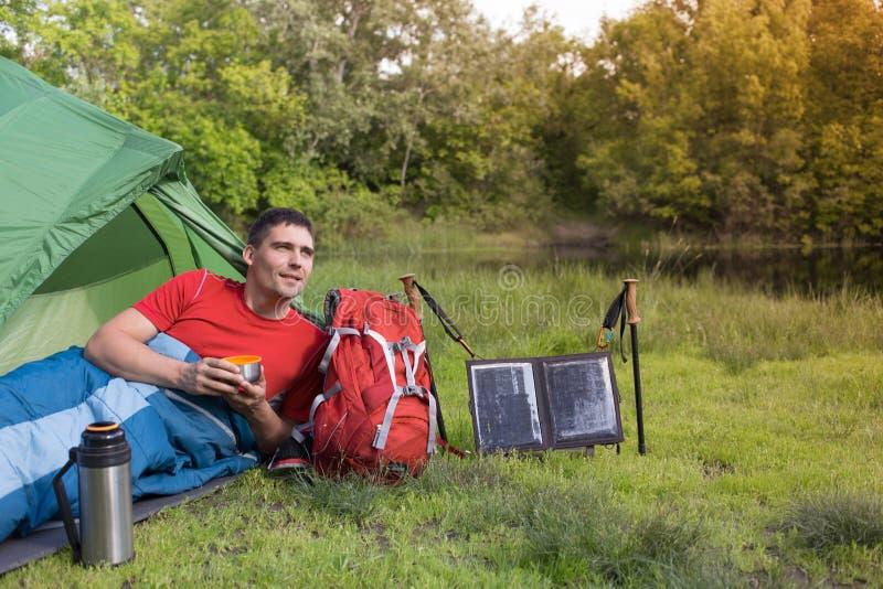 El hombre en el sitio para acampar en el bosque imagen de archivo libre de regalías
