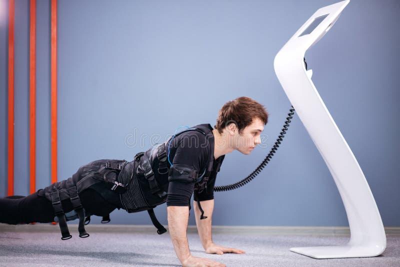 El hombre en el estímulo muscular eléctrico se adapta a hacer ejercicio del tablón ems fotografía de archivo libre de regalías