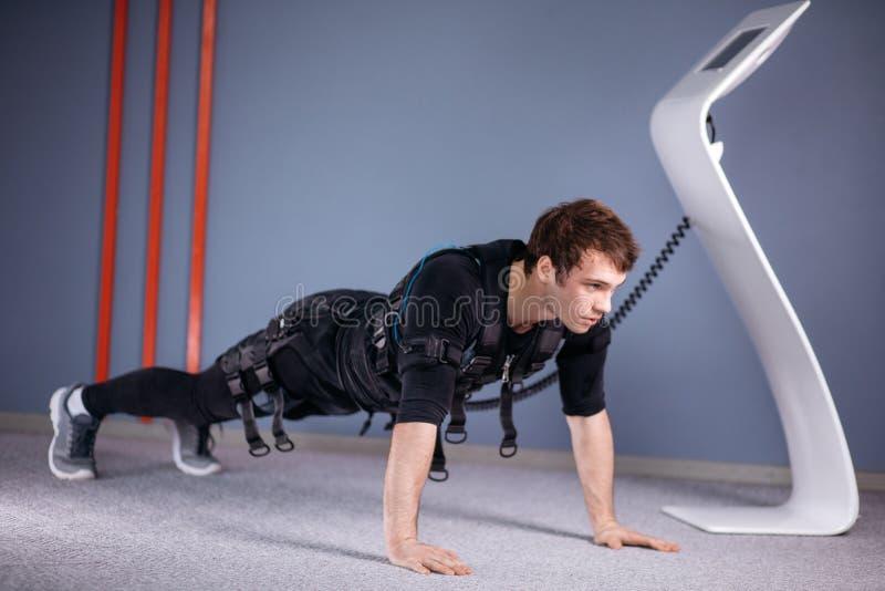 El hombre en el estímulo muscular eléctrico se adapta a hacer ejercicio del tablón ems foto de archivo