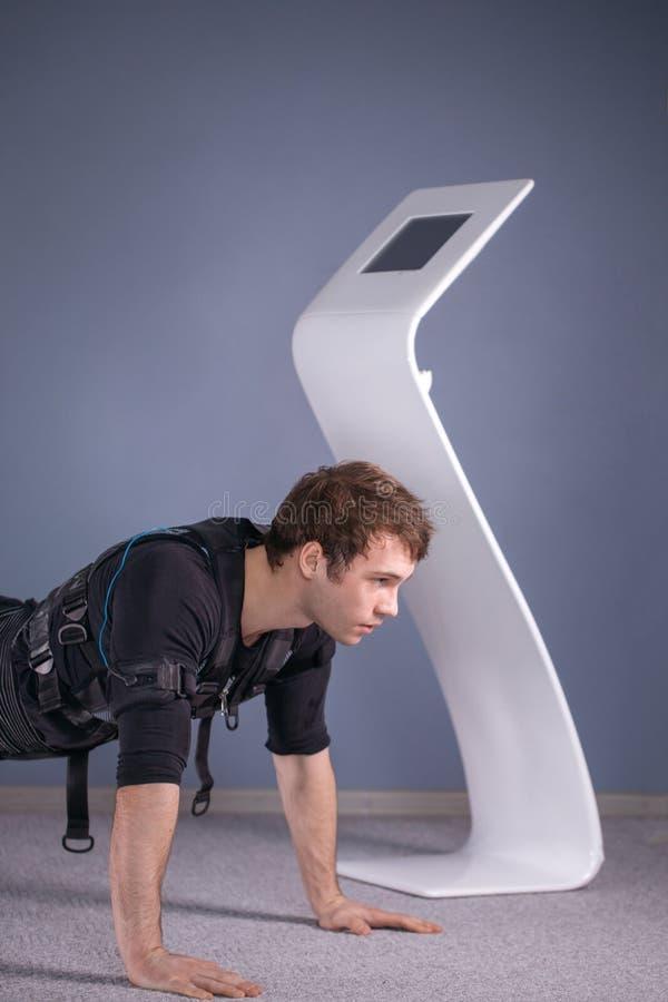 El hombre en el estímulo muscular eléctrico se adapta a hacer ejercicio del tablón ems foto de archivo libre de regalías