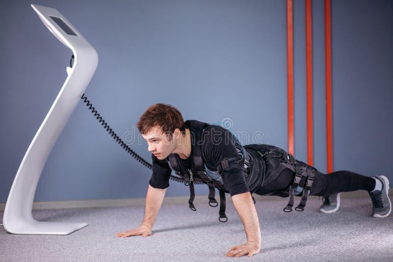 El hombre en el estímulo muscular eléctrico se adapta a hacer ejercicio del tablón ems fotos de archivo