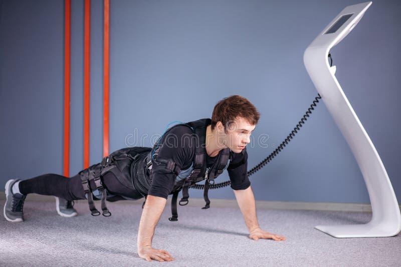 El hombre en el estímulo muscular eléctrico se adapta a hacer ejercicio del tablón ems fotos de archivo libres de regalías