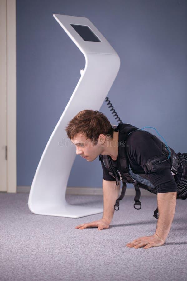 El hombre en el estímulo muscular eléctrico se adapta a hacer ejercicio del tablón ems imagen de archivo