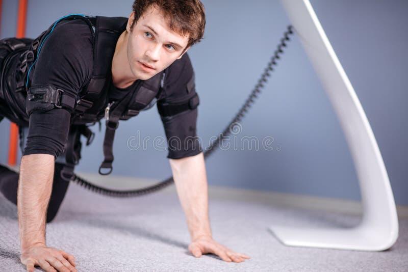 El hombre en el estímulo muscular eléctrico se adapta a hacer ejercicio del tablón ems fotografía de archivo
