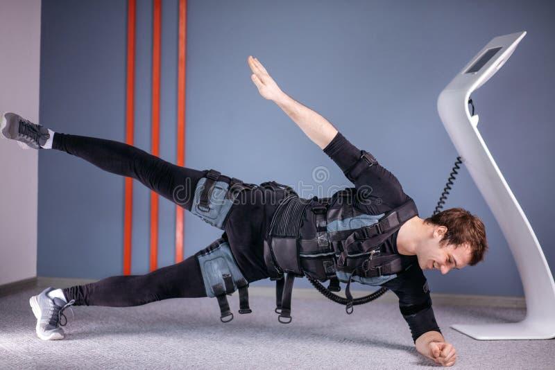 El hombre en el estímulo muscular eléctrico se adapta a hacer ejercicio lateral del tablón ems fotos de archivo libres de regalías