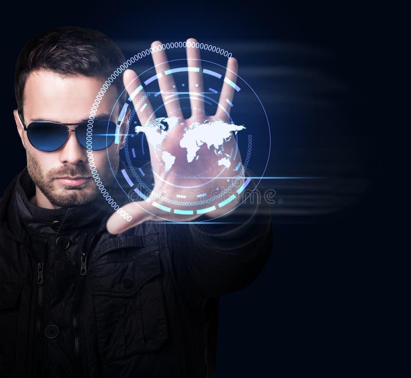 El hombre en gafas de sol controla el sistema virtual con el mapa del mundo fotos de archivo