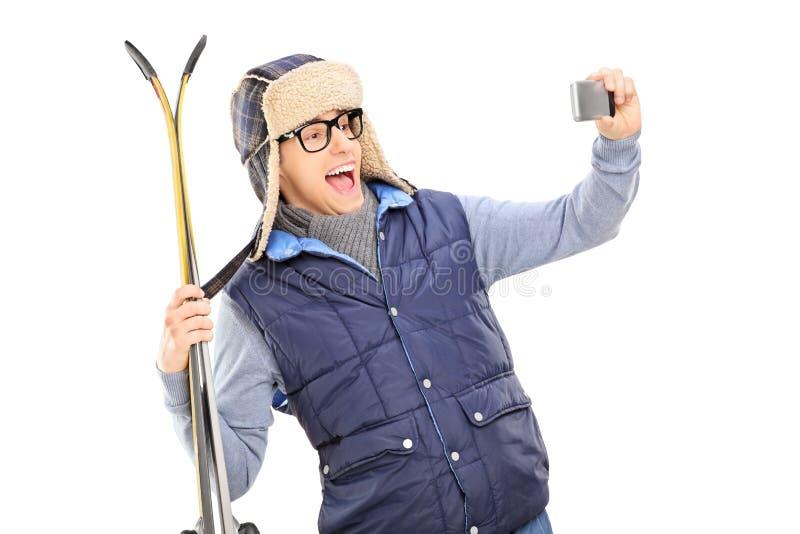 El hombre en invierno viste tomar un selfie con los esquís imagen de archivo