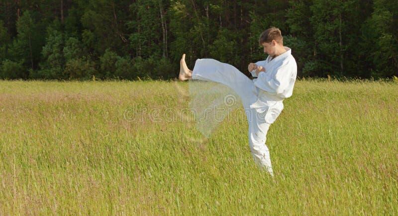 El hombre en kimono satisface soplos por los pies en campo fotos de archivo