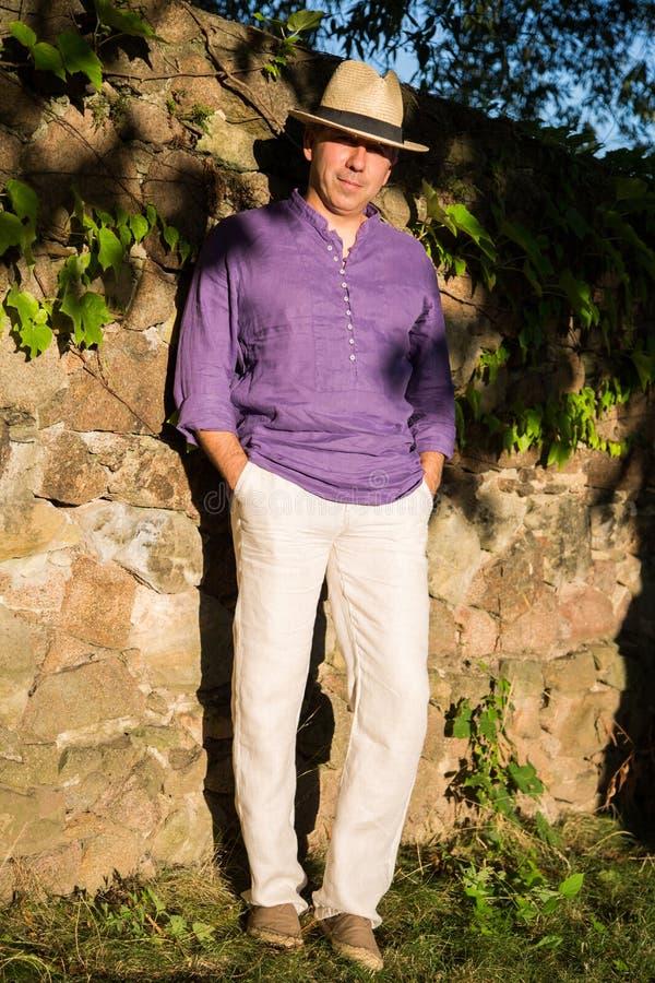 El hombre en la camisa de lino y el sombrero de paja se coloca cerca de la pared de piedra fotos de archivo