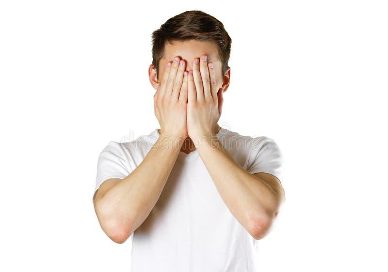 El hombre en la camiseta blanca que cubre su cara con entrega el CCB blanco fotografía de archivo