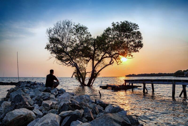 el hombre en la depresión frustrada que se sienta solamente en la presa de la roca exten fotos de archivo libres de regalías
