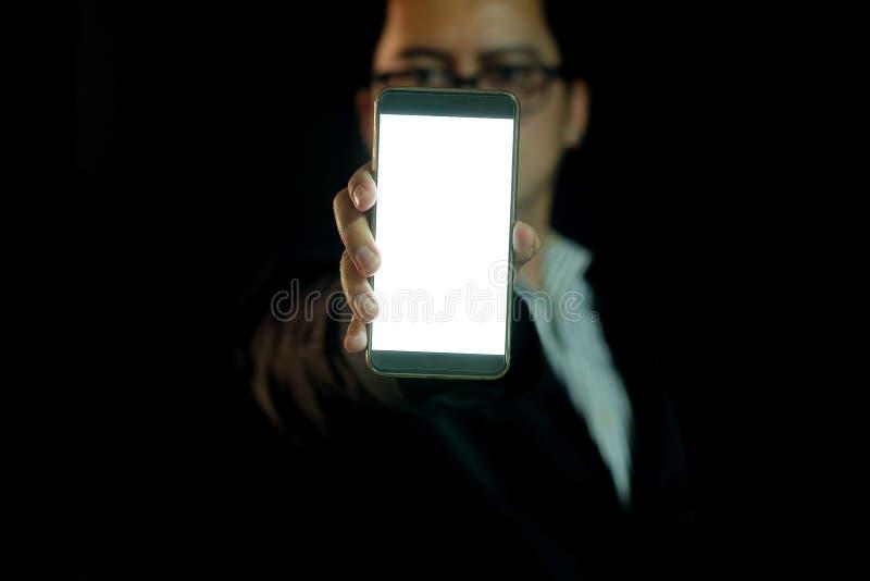 El hombre en la oscuridad muestra el teléfono elegante imagenes de archivo